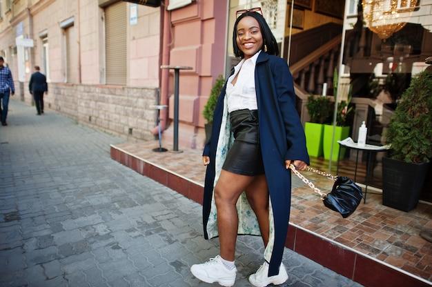 Garota de negócios chique africana em casaco com bolsa. retrato de rua na moda da mulher afro-americana.