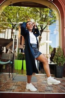Garota de negócios chique africana em casaco e óculos escuros. retrato de rua na moda da mulher afro-americana.
