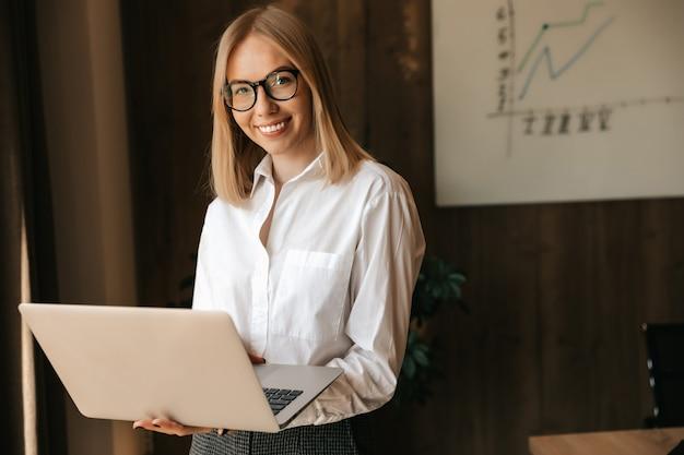 Garota de negócios com um lindo sorriso tem um laptop nas mãos, trabalho de escritório.