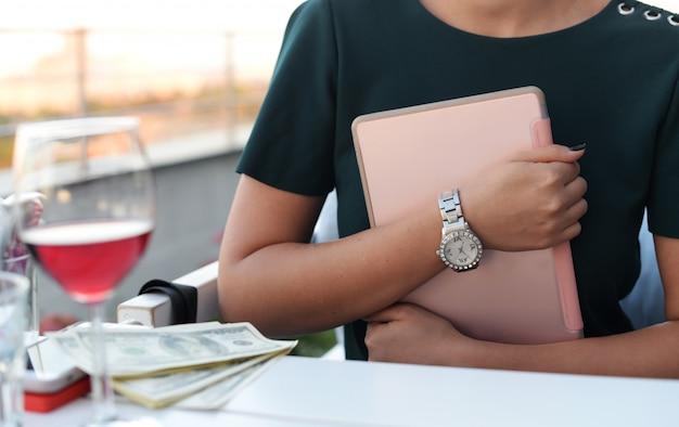 Garota de negócios com um tablet nas mãos, sentado em uma mesa em um res