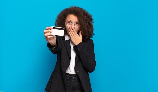 Garota de negócios de adolescente muito afro com um cartão de crédito. conceito de compras online