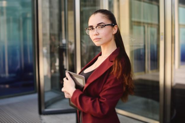 Garota de negócios em copos com tablet computador nas mãos no fundo do edifício de escritórios