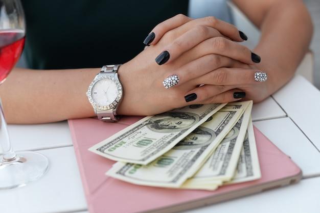 Garota de negócios em um restaurante se senta em uma mesa com um dólares de dinheiro de tablet