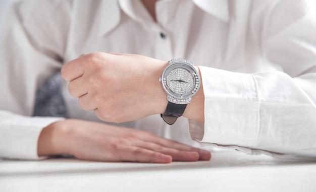 Garota de negócios, mostrando seu relógio de pulso.