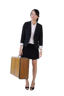 Garota de negócios único segurando a velha mala de viagem com expressão solitária, retrato de corpo inteiro isolado no fundo branco.