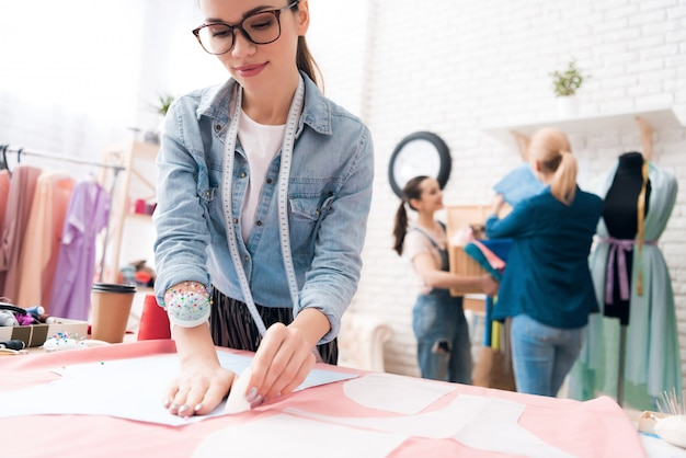 Garota de óculos com medidor no pescoço desenha contornos.