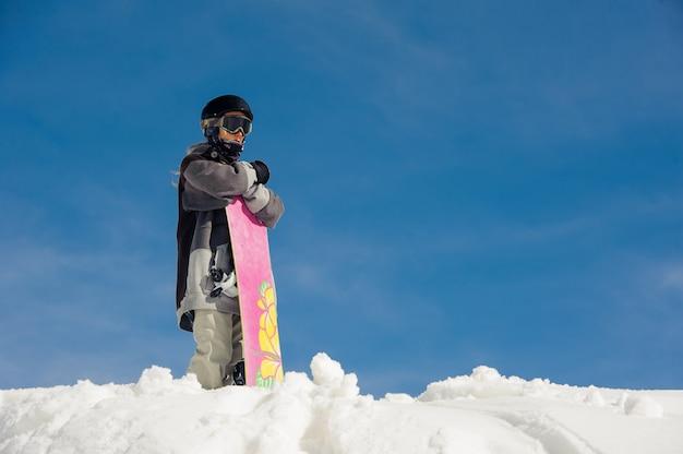 Garota de óculos de esqui e equipamento de esqui fica na neve contra o céu azul