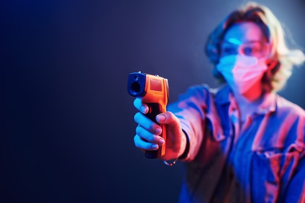 Garota de óculos de proteção e máscara segurando o termômetro infravermelho. luzes de neon