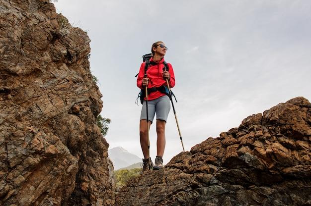 Garota de óculos de sol em pé sobre a rocha com caminhadas mochila e bengalas
