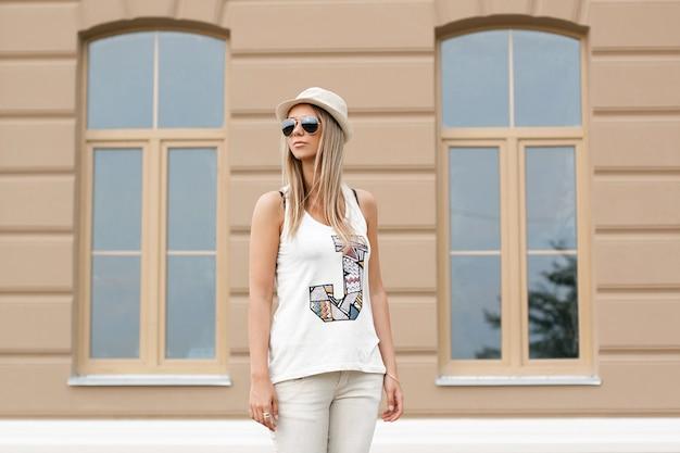 Garota de óculos escuros e chapéu em pé perto de um prédio