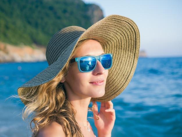 Garota de óculos escuros e um chapéu na praia