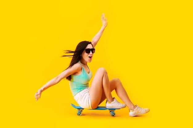 Garota de óculos escuros, sentada em um skate, sobre o espaço amarelo
