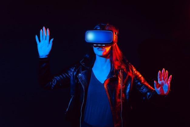 Garota de óculos modernos de realidade virtual em um fundo preto