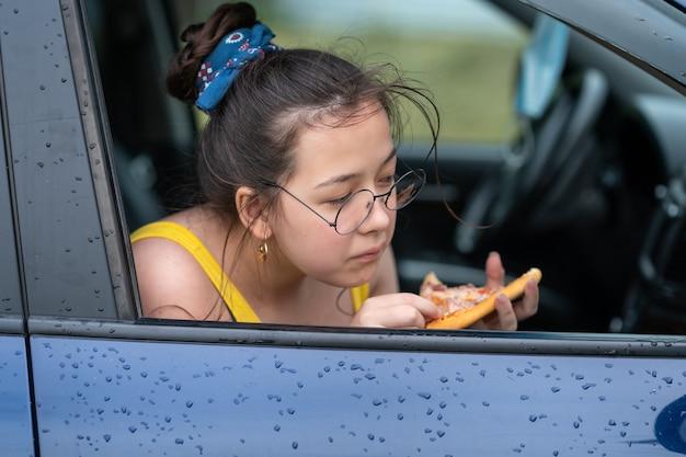 Garota de óculos sentada no carro comendo pizza conceito de viagem por estrada