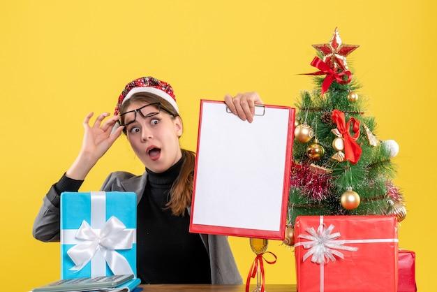 Garota de olhos arregalados com chapéu de natal sentada à mesa, de frente para a frente, tirando os óculos árvore de natal e coquetel de presentes