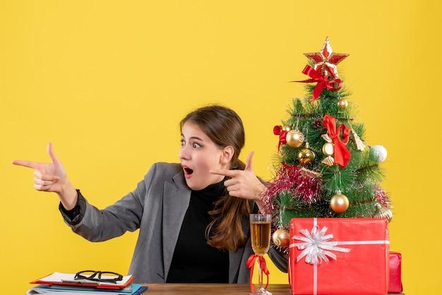 Garota de olhos arregalados de frente, sentada à mesa, apontando com o dedo algo árvore de natal e coquetel de presentes