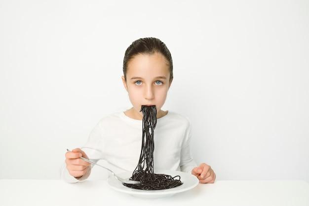 Garota de olhos azuis em uma camisa branca comendo espaguete preto em uma parede branca