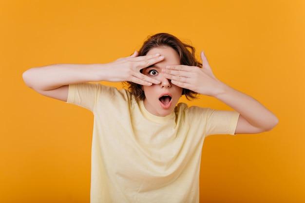Garota de olhos escuros surpresa com anel engraçado posando na parede laranja. mulher morena pálida em uma camiseta amarela, cobrindo o rosto e expressando espanto.