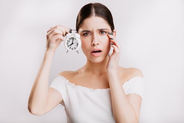 Garota de olhos verdes animada na parede branca. mulher alarmada com a transitoriedade do tempo.