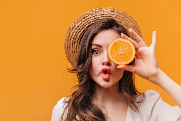 Garota de olhos verdes no velejador está fazendo cara e cobre os olhos com meia laranja.
