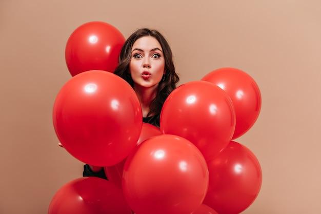 Garota de olhos verdes olha para a câmera com surpresa, segurando balões vermelhos em fundo bege.