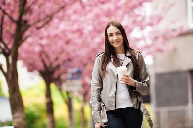 Garota de ótimo humor, posando para uma xícara de café sobre fundo de sakura. mulher morena perto de sakura