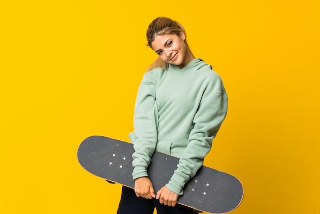 Garota de patinadora adolescente loira sobre amarelo isolado