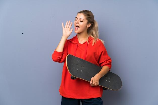 Garota de patinadora adolescente loira sobre gritos de parede cinza com a boca aberta
