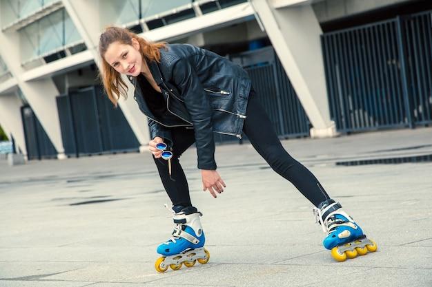 Garota de patins em pé na construção de plano de fundo. jovem cabe garota de mulheres em óculos de sol azuis, jeans e jaqueta de patins, andando ao ar livre depois da chuva.