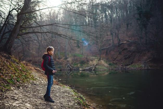 Garota de pé à beira do lago de montanha