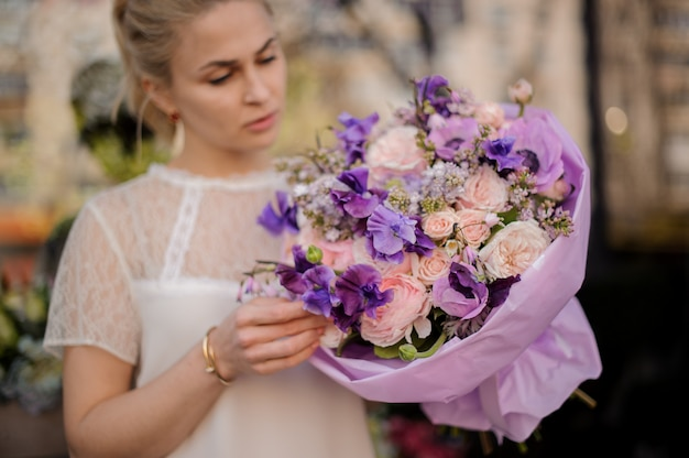 Garota de pé ao ar livre com buquê de flores surpreendente