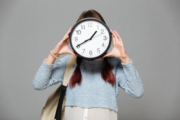 Garota de pé cobrindo o rosto com relógio