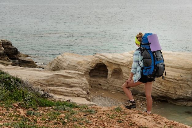 Garota de pé com o pé na rocha segurando mochila caminhadas olhando para o mar