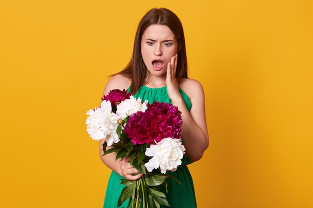 Garota de pé com um buquê de peônias brancas e bordô nas mãos, vestindo um vestido verde, posando com a boca aberta, surpreendeu a expressão facial, isolada em amarelo.