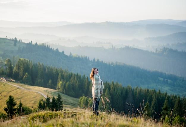 Garota de pé em uma colina contra a bela paisagem montanhosa