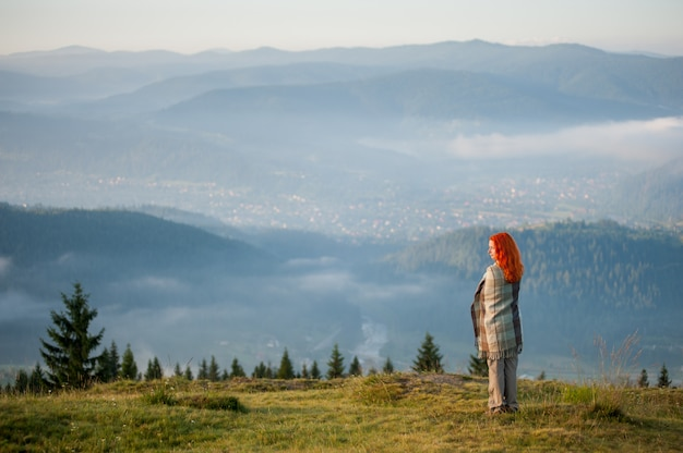 Garota de pé em uma colina contra a paisagem de montanha