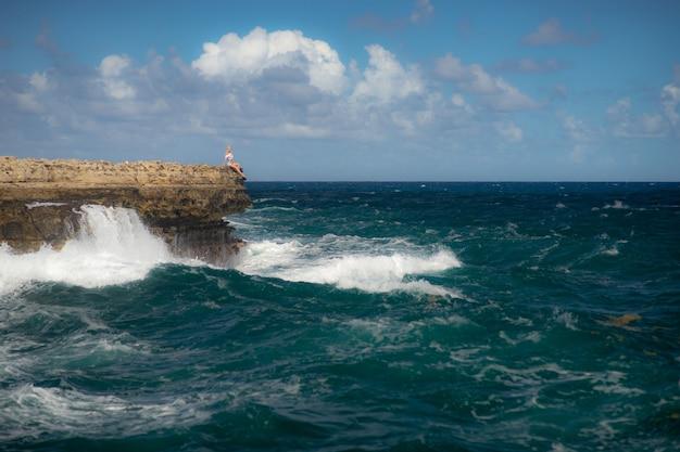 Garota de pé na beira da baía de devil's bridge - mar tropical do caribe - antígua e barbuda. conceito de liberdade e poder