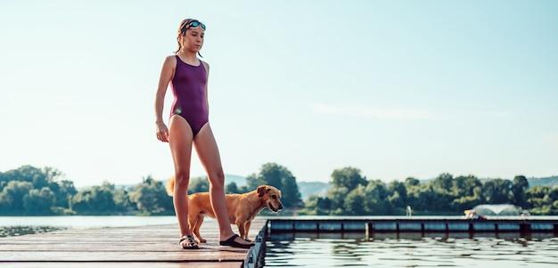 Garota de pé na doca com cachorro pelo rio
