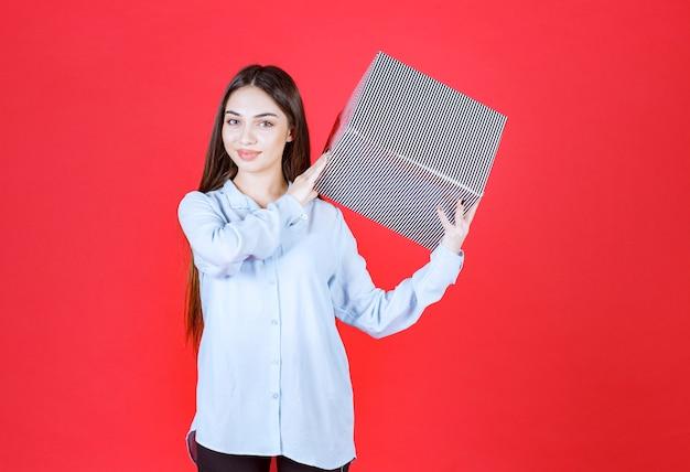 Garota de pé na parede vermelha e segurando uma caixa de presente de prata.