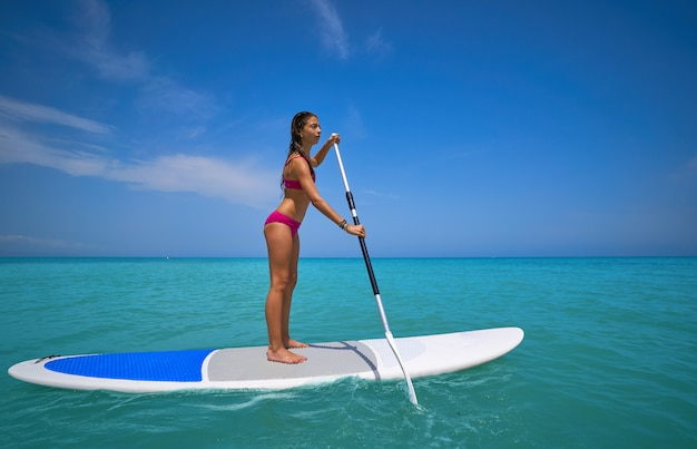 Garota de pé na prancha de surf paddle