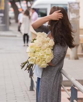 Garota de pé na rua com um buquê de rosas brancas