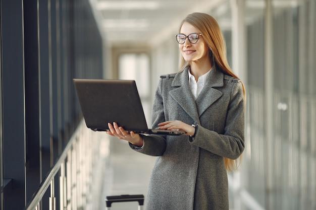 Garota de pé no escritório com um laptop