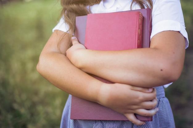 Garota de pé segurando livros nos braços