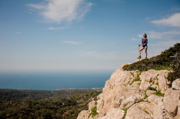 Garota de pé sobre a rocha em shorts com bengalas
