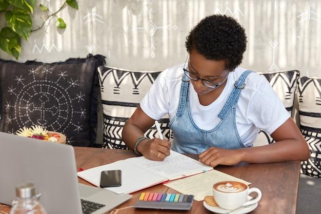 Garota de pele escura com penteado curto, vestida com camiseta branca e jeans sarafan