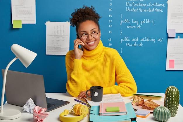 Garota de pele escura positiva faz ligação telefônica, discute melhorias e desenvolvimento de projeto empresarial, vestida de suéter amarelo, olha de lado, posa contra fundo azul