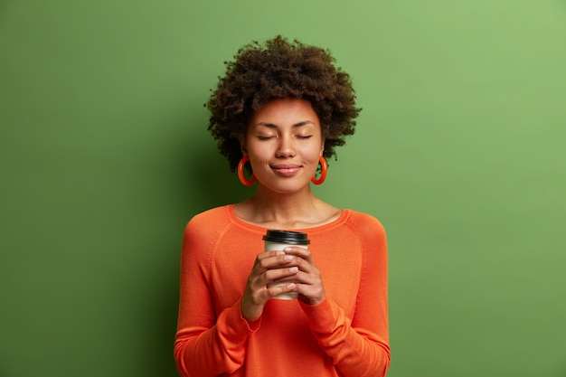 Garota de pele escura satisfeita com cabelo afro segurando um copo de papel com café quente, fecha os olhos e usa um macacão laranja