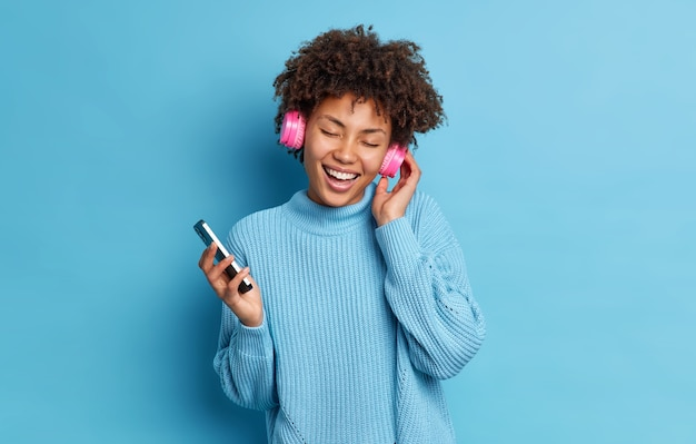 Garota de pele escura usa fone de ouvido dançando em festa techno segurando smartphone fecha os olhos com sorrisos de prazer usa suéter casual