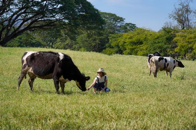 Garota de pensamento positivo. feliz por cuidar do rebanho leiteiro na fazenda