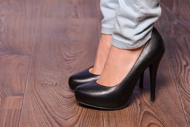 Garota de pernas compridas em sapatos pretos com salto alto no chão de madeira